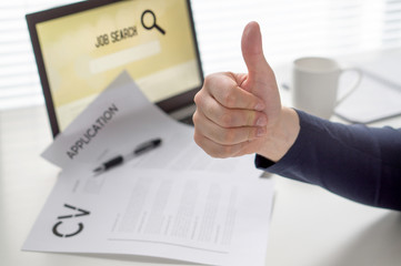 Thumbs up for job search. Applicant with positive attitude. Happy jobseeker. Cheerful man pleased with finding work. Hired or motivated job seeking person. Successful employment concept.