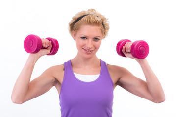 Attraktive blonde Frau trainiert gern mit ihren Hanteln