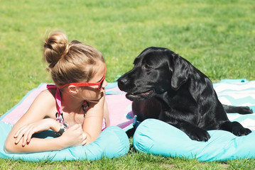 Young girl with her dog outdoor in a sunny day.