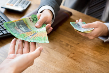 Businessman giving money (australian dollars) at working desk