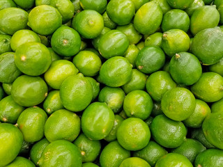whole limes pile display in produce aisle