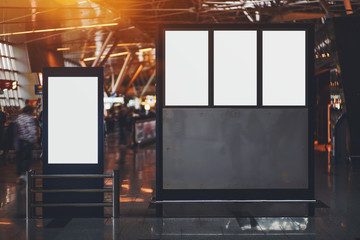 Blank four electronic departures and arrival informational billboards with clean space for publicity content or messages, narrow advertising mock-up placeholders in interior in airport terminal hall