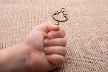 Hand holding a retro styled key