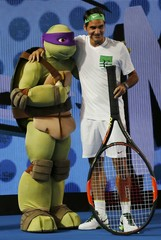 Switzerland's Federer poses with a character from Teenage Mutant Ninja Turtles during Kids Tennis Day at Melbourne Park, Australia