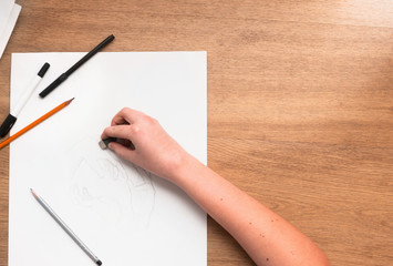 From above hand of a person applying rubber on a draw. Horizontal indoors shot. Drawing lessons, art school, young artist concept