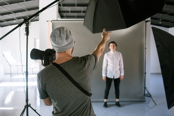 Back view of unrecognizable casual male photographer showing and explaining to the model while studio shooting. Lookbook photoshoot backstage