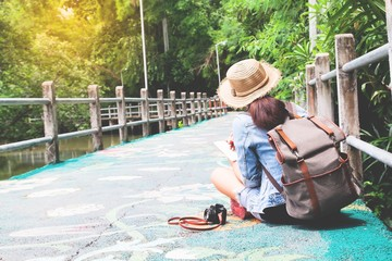 Happy asian backpacker sitting on beautiful walk way with nature, Summer travel concept