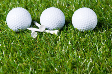 Three white balls lie on a lawn for playing golf as a background