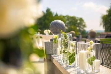 Tall vases with candles and white roses stand on the porch over the lake
