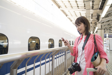 A woman is waiting for a bullet train while watching a smartphone