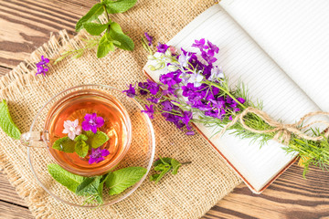Glass cup of summer herbal tea with fresh mint and field larkspur. Bouquet of wild flowers on the notebook. Wooden table. Shallow depth of field.