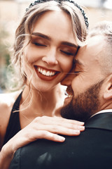 Happy woman with stunning red lips hugs her bearded man tender
