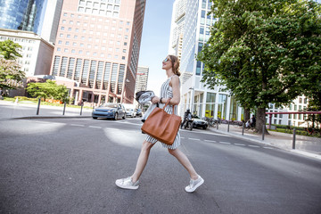 Businesswoman dressed casual crossing the street in the modern district in Frankfurt city