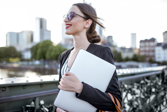 Portrait of a young businesswoman with laptop standing on the bridge in Frankfurt city