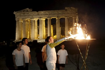 Three-time gold Olympic weightlifting medalist Dimas lights a cauldron with the Olympic Flame, as his children stand by, atop the Acropolis hill as the Parthenon temple is seen in the background in Athens