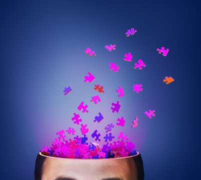 Concept of thinking. Brainstorm. Parts of puzzle exploding from cut of head. 3d illustration