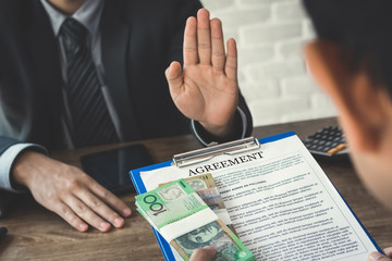Businessman refusing money, Australian dollars,  that come with contract document