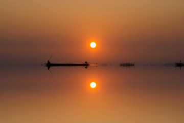 Mirror image of silhouette fisherman with sunset sky on the lake.