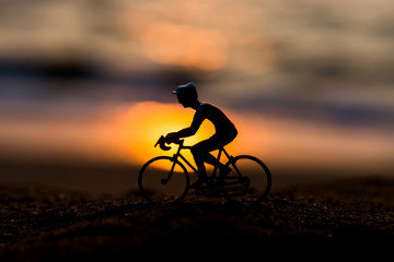 Silhouettes model of cyclists on the beach with sunset.