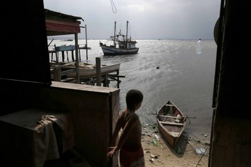 A boy throws a plastic bottle into Guanabara Bay in Rio de Janeiro
