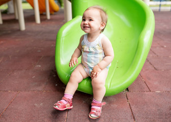 One Year Old Little Baby Girl Playing At Playground Outdoors In Summer