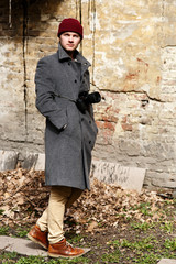 Man in grey coat looks over his shoulder posing before ruined wall