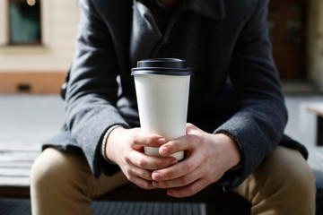 White paper cup of coffee to-go in man's arms