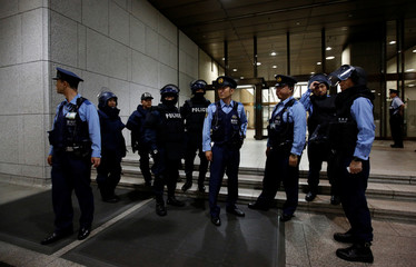 Tokyo Metropolitan Police Department officers wearing protective suits take part in an anti-terror security drill, in which men carrying mock guns and explosive materials attempt to attack the Bank of Japan (BOJ), at BOJ headquarters building in Tokyo