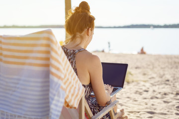 Young woman using a laptop at the beach