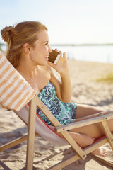 Woman relaxing on a beach chatting on a mobile