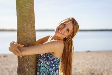 Cute friendly woman hugging tree trunk