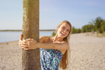 Laughing young woman hanging on to a tree