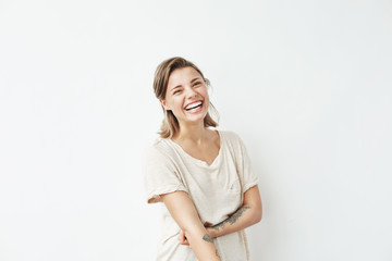 Cheerful happy young beautiful girl looking at camera smiling laughing over white background. Wall mural