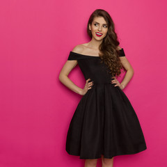 Elegany Young Woman In Black Cocktail Dress Is Looking Away