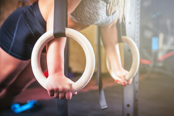 Woman working out with gymnastic rings at crossfit gym