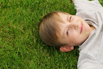 Cute young boy resting on the green grass - summer time, picnic