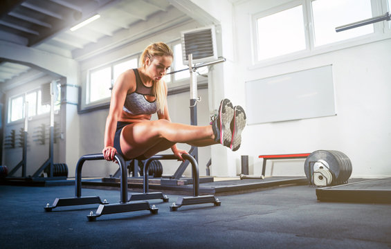 Fitness woman doing L Sit position on parallel bars calisthenic workout