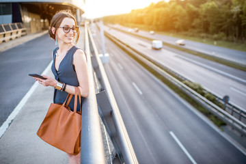 Portrait of a young businesswoman standing with phone on the highway during the business trip on the sunset