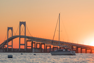 Sunset over Newport Bridge in Newport, Rhode Island.  There is a sailboat moored in front of the Newport Pell Bridge