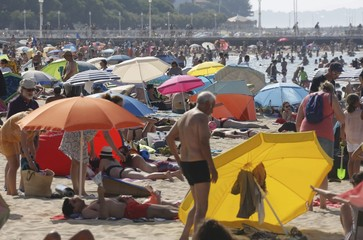 People gather near beach umbrellas as warm summer temperatures continue in Arcachon