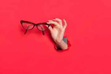 Female hand in paper hole with glasses Wall mural