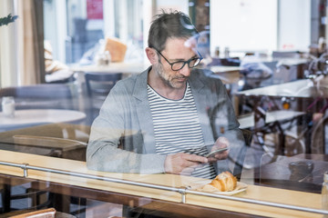 Mature man sitting behind window pane of a coffee shop looking at cell phone