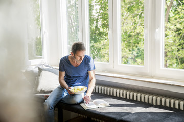 Mature man with book at home