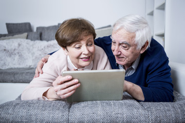 Senior couple lying on couch using digital tablet