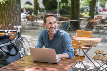 Portrait of smiling mature man using laptop in beer garden
