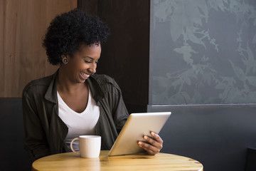 Laughing young woman sitting in a coffee shop looking at tablet