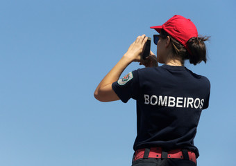 A firefighter takes a picture during a break from fighting a forest fire in Alto da Louriceira