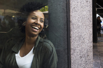 Portrait of laughing young woman looking through window of a cafe