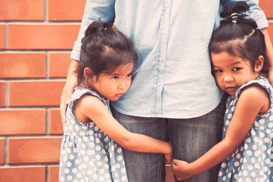 Two sad asian kid girls hugging her mother leg together in vintage color tone