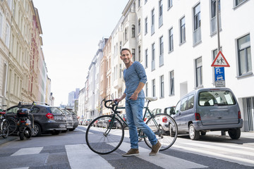 Portrait of smiling mature man with bicycle crossing the street